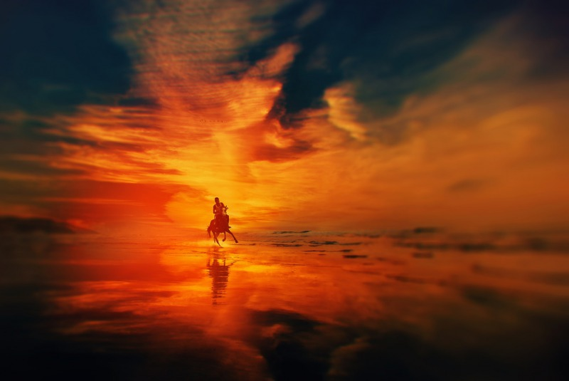 夕日の中で馬に乗る男性